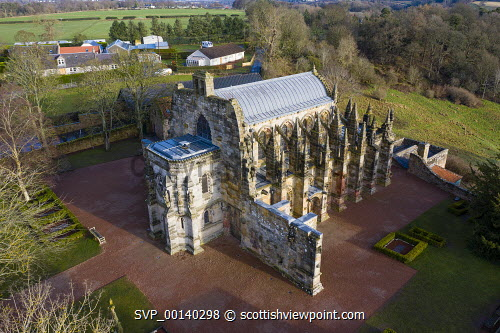 Aerial view of Rosslyn Chapel in Roslin village Midlothian, Scotland, UK Rosslyn Chapel Scotland,Roslin,Rosslyn Chapel,aerial,drone,from above,scottish culture,Scotland,Scottish church,curches,old,UK,united kingdom,britain,historical monument,travel,tourism,da vinci code moview  location,scotland Rosslyn Chapel
