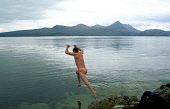 A BRAVE SKINNY DIPPER TAKES THE PLUNGE INTO THE CALM WATERS OF LOCH BROOM, WITH A VIEW ACROSS TO THE MOUNTAINS OF COIGACH BEYOND, HIGHLAND. Pic: Chris Robson/Scottish Viewpoint This picture may not be... COAST,REMOTE,PEOPLE,NUDE,LEAP,JUMP,SWIMMING,NAKED,REFLECTION,MOUNTAIN,WATER
