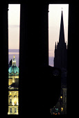 LOOKING OVER TO THE BANK OF SCOTLAND HEADQUARTERS ON BANK STREET AND THE SPIRE OF ST. JOHN OF THE TOLBOOTH (THE HUB) FRAMED BY THE SILHOUETTE OF THE PILLARS OF THE NATIONAL MONUMENT ON CALTON HILL, ED...