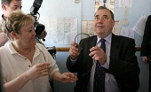 SNP Leader Alex Salmond MP on the campaign trail visits a taxi hire control room wearing a telephone headset in East Kilbride old town centre, pictured with Connie Madden controller   1/05/07 ALLAN MI... SCOTLAND,POLITICS