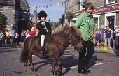 Young child riding a Shetland pony with mum leading during the  Langholm Common Riding, Dumfries and Galloway. PIC : ALLAN DEVLIN/SCOTTISH VIEWPOINT  Tel: +44 (0) 131 622 7174  Fax: +44 (0) 131 622 71... ALLAN DEVLIN/SCOTTISH VIEWPOINT langholm,common,riding,ride,out,outs,young,child,on,horse,back,shetland,pony,mum,mother,parent,equestrian,event,sport,sports,horses,town,centre,crowd,people,traditional,tradition,dumfriesshire,scotlan