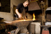 Ross Berry of Kaos Blacksmiths working in his forge with a wrought iron hammer and red hot metal at Drumlanrig Castle, Nithsdale, Dumfries and Galloway, Scotland UK  PIC: ALLAN DEVLIN/SCOTTISH VIEWPOI... blacksmith,work,workshop,worker,workmanship,hammering,craft,craftmanship,anvil,fire,heat,sparks,spark,sparking,speed,forged,interior