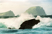 WAVES CRASH OVER A ROCK (IN THE DISTANCE IS THE CAMBIR, SOAY STAC AND THE BULK OF SOAY) FROM HIRTA, ONE OF THE ISLANDS IN THE ST. KILDA ARCHIPELAGO - A NATURE RESERVE IN THE HANDS OF THE NATIONAL TRUS... COAST,WATER,SUNNY,ISLAND