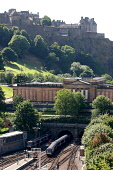 Looking down to a train emerging from the tunnel under the Mound as it approaches Waverley Station, with the National Gallery of Scotland and Edinburgh Castle visible, in the city centre of Edinburgh.... COLINMCPHERSON/SCOTTISHVIEWPOINT PRINCES STREET GARDENS,TRANSPORT,TRAINS,SUNNY,SUMMER,RAILWAY