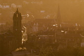 EARLY MORNING VIEW OF THE SCOTTISH BORDERS TOWN OF PEEBLES, WITH IN THE FOREGROUND THE OLD PARISH CHURCH DOMINATING THE HIGH STREET, APRIL. horizontal,town,settlement,community,building,buildings,history,historic,ancient,spring,trees,smoke,steam,sunrise