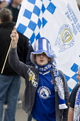 Football Scottish Cup Final fan in his teams colour flag funny hat and flag making is way to Hampden Park Glasgow Scotland UK PIC: ALLAN DEVLIN/SCOTTISH VIEWPOINT Tel: +44 (0) 131 622 7174   Fax: +44... ALLAN DEVLIN/SCOTTISHVIEWPOINT scottish,cup,final,2008,football,soccer,scotland,queen,of,the,south,dumfries,doonhamers,fan,crowd,supporter,support,party,time,queens,qos,team,colours,flag,funny,hat,costume,top,scarf,dress,excited,ex