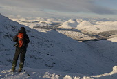 HILLWALKER AND VIEW TOWARDS STRATH FILLAN (ROAD BETWEEN CRIANLARICH AND TYNDRUM) AND THE FIVE CORBETTS OF BEINN ODHAR (DISTANT CENTRE RIGHT), BEINN CHAORACH, CAM CHREAG, BEINN NAM FUARAN AND BEINN A'... PUBLIC, MR horizontal,dramatic,grandeur,Highlands,hillwalker,hillwalking,inspiring,isolation,landscape,lonely,majestic,mountain,mountains,peaceful,remote,scenic,Scottish Highlands,uplands,walker,snow,snowfall,su