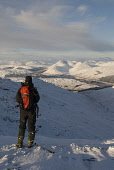 HILLWALKER AND VIEW TOWARDS STRATH FILLAN (ROAD BETWEEN CRIANLARICH AND TYNDRUM) AND THE FIVE CORBETTS OF BEINN ODHAR (DISTANT CENTRE), BEINN CHAORACH, CAM CHREAG, BEINN NAM FUARAN AND BEINN A' CHAIST... PUBLIC, MR dramatic,grandeur,Highlands,hillwalker,hillwalking,inspiring,isolation,landscape,lonely,majestic,mountain,mountains,peaceful,remote,scenic,Scottish Highlands,uplands,walker,snow,snowfall,sunny,blue,wh