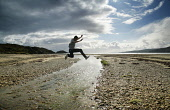 A boy jumps a stream on the beach at Carradale, on the western coast of the Kintyre peninsula, Argyll and Bute. PIC: IAIN MCLEAN/SCOTTISH VIEWPOINT Iain McLean,kintyre,carradale,beach,sand,sandy,coastal,coast,water,sea,walk,LEISURE,ACTIVITY,son,daughter,mother,sun,sunny,food,eat,eating,Al fresco,ACTION,FUN,JUMP