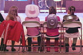 Creetown Country Music Festival young girls near stage sitting in seats with cowgirl hats on backs, Dumfries and Galloway Scotland. PIC: ALLAN DEVLIN/SCOTTISH VIEWPOINT Tel: +44 (0) 131 622 7174  Fax:... Public, NMR gaelforce,gael,force,creetown,country,music,festival,cowgirls,hat,sit,sitting,girl,stage,cowboys,arts,entertainment,dumfries,galloway,scotland,event