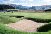 LOOKING ACROSS A BUNKER TO TWO GOLFERS ON THE FAIRWAY AT THE MONARCHS GOLF COURSE AT GLENEAGLES- ONE OF TWO COURSES WITHIN THE COMPLEX OF THE GLENEAGLES HOTEL, PERTH & KINROSS. PIC: G.SATTERLEY/SCOTTI... Public, NMR FORESTRY,ACTIVITY,SPORT,HILLS,SUNNY,SUMMER