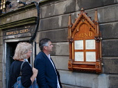 A couple browsing the menu outside The Witchery restaurant and hotel. PIC:GARRY MCHARG/SCOTTISH VIEWPOINT  Tel: +44 (0) 131 622 7174  Fax: +44 (0) 131 622 7175  E-Mail : info@scottishviewpoint.com  Th... Public, NMR accommodation,eat,eatery,eating,edinburgh,food,hotel,old town,scotland,scottish,sign,signage,view,viewing.