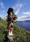 LOCH NESS INVERNESSSHIRE Scottish piper bagpipes tartan kilt uniform lochside near Drumnadrochit  Pic: Doug Houghton / Scottish Viewpoint Tel: +44 (0) 131 622 7174 Fax: +44 (0) 131 622 7175 E-Mail: in... Public bagpipes,traditional,highlander,tartan,kilt,piper,scotland,scottish,kilts,ceremonial,dress,costume,uniform,sporran,bag,pipe,bagpiper,music,instrument,musical,musicial,play,performer,custom,culture,sco