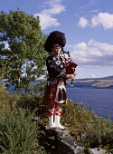 LOCH NESS INVERNESSSHIRE Scottish piper bagpipes tartan kilt uniform lochside near Drumnadrochit  Pic: Doug Houghton / Scottish Viewpoint Tel: +44 (0) 131 622 7174 Fax: +44 (0) 131 622 7175 E-Mail: in... Public highlander,tartan,kilt,bagpiper,scotsman,national,instrument,scotland,scottish,kilts,ceremonial,dress,costume,uniform,sporran,bag,pipe,music,musical,musicial,playing,performer,custom,culture,scot,outf