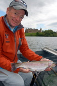 Fly fishing on Linlithgow Loch, West Lothian The catch PIC: Scott Whitelaw / Scottish Viewpoint TEL: +44 (0) 131 622 7174 FAX: +44 (0) 131 622 7175 E-MAIL: info@scottishviewpoint.com WEB: www.scottish... Public, NMR fish,boat,fishing,angling,angler,fisherman,people