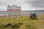 A couple on a bench next to warning signs at Chanonry Point, overlooking the Moray Firth in the Highlands of Scotland. Pic: Allan Coutts / Scottish Viewpoint Tel: +44 (0) 131 622 7174 Fax: +44 (0) 131... Public, NMR Chanonry Point,lighthouse,Moray Firth,Inverness,Highlands,Higland,Council,Ross,Cromarty,coast,coastal,sea,tide,currents,water,danger,swimming,bathing,dangerous,warning,beach,tourism,tourist,vacation,s