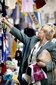 A TOURIST PERUSES ITEMS FOR SALE AT A GIFT SHOP ON CASTLEHILL / THE HIGH STREET , EDINBURGH. PIC: P.DODDS /SCOTTISH VIEWPOINT Tel: +44 (0) 131 622 7174   Fax: +44 (0) 131 622 7175 E-Mail : info@scotti... Public, NMR OLD TOWN,TOURISM,SUNNY,SHOPPING,SCOTLAND,RETAIL,PEOPLE