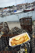 Fish 'n' chips from the Anstruther Fish Bar pictured by the harbour, Anstruther, East Neuk of Fife. Picture Credit: Chris Robson / Scottish Viewpoint Tel: +44 (0) 131 622 7174 Fax: +44 (0) 131 622 717... Public 2010,summer,food,eating,famous,award,winning,renowned,cafe,restaurant,boats,fish and chips