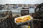 Fish 'n' chips from the Anstruther Fish Bar pictured by the harbour, Anstruther, East Neuk of Fife. Picture Credit: Chris Robson / Scottish Viewpoint Tel: +44 (0) 131 622 7174 Fax: +44 (0) 131 622 717... Public 2010,summer,food,eating,famous,award,winning,renowned,cafe,restaurant,fish n chips,boats