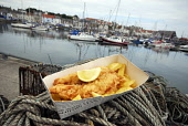 Fish 'n' chips from the Anstruther Fish Bar pictured by the harbour, Anstruther, East Neuk of Fife. Picture Credit: Chris Robson / Scottish Viewpoint Tel: +44 (0) 131 622 7174 Fax: +44 (0) 131 622 717... Public fish and chips,boats,restaurant,renowned,winning,food,summer,2010,dine,cafe,famous,dining
