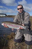 Angler Willie Brash with a large rainbow trout Picture Credit: Scott Whitelaw / Scottish Viewpoint Tel: +44 (0) 131 622 7174   Fax: +44 (0) 131 622 7175 E-Mail : info@scottishviewpoint.com Web: www.sc... Public, MR summer,fishing,rod,angling,fisherman,fishermen,angler,anglers,reel,fish
