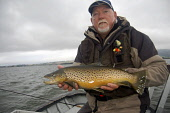 Angler Bill with a large brown  trout, Loch Leven Picture Credit: Scott Whitelaw / Scottish Viewpoint Tel: +44 (0) 131 622 7174   Fax: +44 (0) 131 622 7175 E-Mail : info@scottishviewpoint.com Web: www... Public, MR summer,fishing,rod,angling,fisherman,fishermen,angler,anglers,reel,fish,boat
