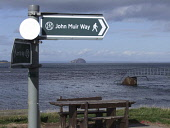 Sign for the John Muir Way, East Lothian Picture Credit: Scott Whitelaw / Scottish Viewpoint Tel: +44 (0) 131 622 7174   Fax: +44 (0) 131 622 7175 E-Mail : info@scottishviewpoint.com Web: www.scottish... Public summer,park,country,walk,sign post,post,bass,rock,sea,picnic table,coastal,belhaven,bay,path