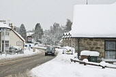 Motor car driving in snowy village houses covered in snow, Carrbridge, Highland. Picture Credit: D. Houghton / Scottish Viewpoint Tel: +44 (0) 131 622 7174   Fax: +44 (0) 131 622 7175 E-Mail : info@sc... Public wintertime,scottish,highlands,village,snow,weather,scotland,rural,villages,roads,motor,car,driving,in,snowy,houses,carrbridge,invernessshire,winter,frost,wintery,frosty,white,day,cold,frozen,community