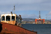 A rusty old boat sits on the shore at Balblair on the Black Isle, looking across the Cromarty Firth to an oil rig at Invergordon, Highland. Picture Credit : Ross Graham / Scottish Viewpoint Tel: +44 (... Public 2011,winter,sunny,water,industry,abandoned