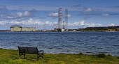 looking across the Cromarty Firth to the fabrication yard at Invergordon from the village of Cromarty, Highlands of Scotland. Picture Credit : Andrew Wilson / Scottish Viewpoint   Tel: +44 (0) 131 622... Public 2012,spring,sunny,water,coast,coastal,highland,production,energy,fuel,drill,drilling,north,sea,industry,industrial,platform,petro,chemical,petrochemical,seat,park,bench