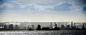 A container ship passing Grangemouth Oil Refinery in the Firth of Forth, viewed from Fife. Picture Credit : Andrew Wilson / Scottish Viewpoint   Tel: +44 (0) 131 622 7174  E-Mail : info@scottishviewpo... Public 2013,winter,sunny,atmospheric,industry,petro,chemical,economy,pollution,silhouette,panoramic