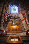 The bell from HMS Royal Oak sunk inside St Magnus Cathedral at Kirkwall, Mainland, Orkney. Credit : Andrew Wilson / Scottish Viewpoint  Tel: +44 (0) 131 622 7174  E-Mail : info@scottishviewpoint.com... Public 2013,interior,island,islands,isle,isles,attraction,visitor,tourist,building,religion,saint,memorial,ship,flag,flags,union,jack,stained,glass,window