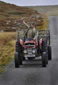 Marko Tayburn (owner of the Abhainn Dearg Distillery) on the road to his distillery at Carnish, Isle of Lewis with a bottle of the limited edition Abhainn Dearg malt whisky due to be launched at this... Public 2011,autumn,manufacture,product,drink,drinking,spirit,western,isles,tractor,smile
