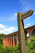 A footpath sign to Broomhill with the Leaderfoot Viaduct - a former railway viaduct over the River Tweed visible behind, near Melrose, Scottish Borders. Picture Credit : Jason Baxter / Scottish Viewpo... Public 2012,summer,sunny,structure,victorian,engineering,historic,scotland,heritage,arch,arches,disused,bridge,countryside,walking,walk,directions