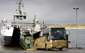 A tour bus disembarking the MV Loch Alainn Caledonian MacBrayne Ferry at the slipway on Eriskay, Outer Hebrides Picture Credit : Mike Clarke / Scottish Viewpoint   Tel: +44 (0) 131 622 7174  E-Mail :... Public 2010,autumn,calmac,cal,mac,vehicle,transport,boat,Western,Isles,island,isle,water,coast,sound,barra,coach,touring,trip