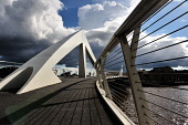The Tradeston Bridge also known as the Squiggly Bridge over the River Clyde, Glasgow.  Picture Credit : Tony Clerkson / Scottish Viewpoint   Tel: +44 (0) 131 622 7174  E-Mail : info@scottishviewpoint.... Public 2012,summer,sunny,atmospheric,urban,city,architecture,structure,engineering,pavement,footbridge,Broomielaw,dark,clouds