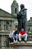 GLASGOW, SCOTLAND, UK: Wellwishers sitting on a statue waiting to greet the Queen in the city's George Square on the first day of her 1000-mile, seven day Golden Jubilee tour of Scotland. Earlier the... Colin McPherson