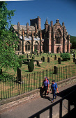 A COUPLE OF WALKERS IN FRONT OF THE IMPRESSIVE RUINS OF MELROSE ABBEY- DATING FROM 1136 WHEN IT WAS FOUNDED BY DAVID I AND THE PLACE OF BURIAL OF ROBERT THE  BRUCE'S HEART, IN THE CENTRE OF MELROSE, S... SUNNY,HERITAGE,HISTORIC SCOTLAND,ARCHITECTURE,BUILDING,RELIGION,GRAVEYARD,CEMETERY,ACTIVITY,WALKING,PEOPLE