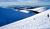 A LONE SKIER DESCENDS THE BUZZARD SKI SLOPE AT THE LECHT 2090 SKI CENTRE AS A SNOWBOARDER CLIMBS BACK TO THE TOP, WITH A VIEW TO MOUNTAINS BEYOND, MORAY. PIC: P.TOMKINS/VisitScotland/SCOTTISH VIEWPOIN... PEOPLE,WINTER,SNOW,ICE,ACTIVITY,MOUNTAIN,SUNNY,SKIING,SNOWBOARDING