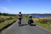 A COUPLE CYCLE TOURING ON ROAD B8001 FROM CLAONAIG  TOWARDS KENNACRAIG, KINTYRE, ARGYLL.  WEST LOCH TARBERT IN DISTANCE.  SPRING 2009 PIC: P. TOMKINS / VISITSCOTLAND / SCOTTISH VIEWPOINT TEL: +44 (0)... Public, NMR 2009,SPRING,BIKES,CYCLES,BICYCLES,TOURERS,TOURING,ACTIVITY,PEOPLE,SUMMER