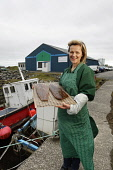 A worker at Salar Smokehouse, holding sides of their award winning Flaky Smoked Salmon, outside the smokehouse at Lochcarnan, Isle of South Uist, Outer Hebrides. Picture Credit: P.Tomkins / VisitScotl... Public, MR island,islands,2010,western isles,summer,isle,food,produce,local,fishing,product