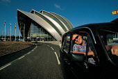 A WELCOMING GLASWEGIAN TAXI DRIVER IN HIS CAB OUTSIDE THE CLYDE AUDITORIUM ALSO KNOWN AS THE ARMADILLO, A PURPOSE BUILT CONFERENCE CENTRE WHICH IS PART OF THE SCOTTISH EXHIBITION AND CONFERENCE CENTRE... BUILDING,SMILE,FRIENDLINESS,TRANSPORT,ARCHITECTURE,CHARACTER,PEOPLE,SUNNY