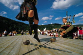 A PARTICIPANT TAKES PART IN THE SWORD DANCING EVENT WHILST A PIPER PROVIDES THE MUSUCAL ACCOMPANIMENT AT THE BALLATER HIGHLAND GAMES, ABERDEENSHIRE. PIC: P. TOMKINS/VisitScotland/SCOTTISH VIEWPOINT Te... TARTAN,CROWD,KILT,STAGE,SUNNY,SUMMER,PEOPLE