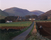 LOOKING ALONG A ROAD THROUGH FARMLAND TOWARDS DURISDEER- A VILLAGE RENOWNED FOR THE SITE OF SEVERAL ROMAN CAMPS, DUMFRIES AND GALLOWAY. PIC: P.TOMKINS/VisitScotland/SCOTTISH VIEWPOINT Tel: +44 (0) 131... FIELD,SHEEP,TRACTOR,SUNNY,EVENING,PLOUGHING,FARMING,SPRING