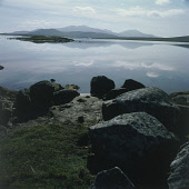LOOKING OVER CALM WATER TO THE MOUNTAINS OF SOUTH UIST FROM NORTH UIST, OUTER HEBRIDES. PIC: P.TOMKINS/VisitScotland/SCOTTISH VIEWPOINT Tel: +44 (0) 131 622 7174   Fax: +44 (0) 131 622 7175 E-Mail : i... ROCKS,COAST,REFLECTION,FORESHORE,SUNNY,MOUNTAIN