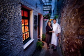 Jimmy and Amanda Graham proprietors since 1981 of Ostler's Close Restaurant - one of Scotland's premier dining experiences, serving the best of local and Scottish seasonal ingredients, Cupar, Fife. Pi... Public 2011,summer,dusk,evening,atmospheric,welcoming,exterior,alley,hanging,basket,flowers,sign,people,smile,owners,chef,food,eating