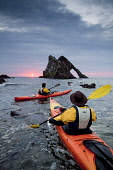 A couple sea kayaking at Bow Fiddle Rock, Portknockie, Moray. Picture Credit : Paul Tomkins / VisitScotland / Scottish Viewpoint  Tel: +44 (0) 131 622 7174  E-Mail : info@scottishviewpoint.com  Web: w... Public, MR 2009,summer,sport,activity,kayak,kayaks,paddle,paddling,people,atmospheric,sunrise,sun,rise,dawn,arch,geological,feature,coast,coastal,water