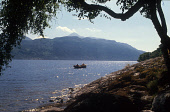 LOOKING SOUTH EAST ACROSS LOCH LOMOND- EXTENDING NORTH FROM BALLOCH TO ARDLUI A DISTANCE OF 24 MILES MAKING IT BRITAIN'S LARGEST STRETCH OF INLAND WATER, WHERE TWO MEN FISH FROM A SMALL BOAT WITH BEN... ACTIVITY,WATER,MUNRO,SUMMER,MOUNTAIN,SUNNY