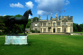 LOOKING PAST AN EQUESTRIAN STATUE TO DALMENY HOUSE- THE 19C MANSION OF THE EARLS OF ROSEBERRY AND SCOTLAND'S FIRST GOTHIC REVIVAL HOUSE DESIGNED BY WILLIAM WILKINS, OVERLOOKING THE FIRTH OF FORTH, DAL... UNION JACK,FLAG,SUNNY,BUILDING,HORSE,ARCHITECTURE,SUMMER