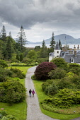 A couple walking in Attadale Gardens, Strathcarron, with the house visible (private) and Loch Carron beyond, Highlands of Scotland.   Picture Credit : Paul Tomkins / VisitScotland / Scottish Viewpoint... Public 2012,summer,water,attraction,visitor,tourist,people,garden,horticulture,drive,view,highland